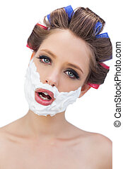 Model in hair curlers with shaving foam in close up on white...