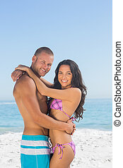 Smiling young couple hugging each other on the beach