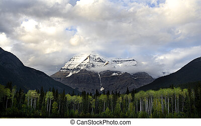 Mt Robson stands over a valley and trees with its head in...
