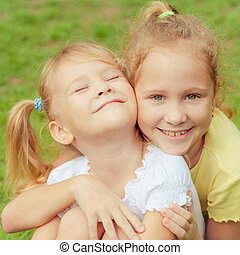 two happy little girls in the park