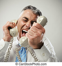 Businessman yelling into phone - A stressed businessman...