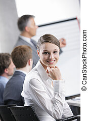Meeting - Smiling woman sitting at a business meeting with...