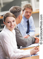 Smiling woman sitting at a business meeting with colleagues...