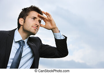 Looking away to a better future - Young Business man looking...