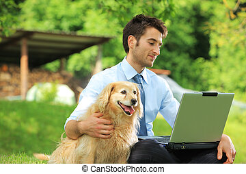 Businessmans best friend - Young business man working...
