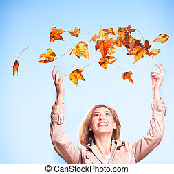 Autumn joy - An attrctive woman happily throws colorful...