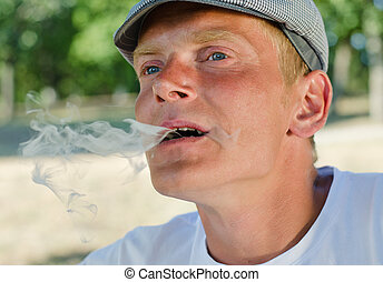 Man blowing smoke out of his mouth - Close up of a man...