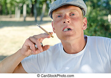 Young man enjoying a cigarette - Young man in a trendy cap...