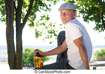Man sitting relaxing with a bottle of alcohol