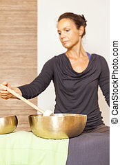 singing bowls - A woman is relaxing with singing bowls on...