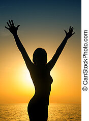 Happy woman silouette in the sunset on the beach