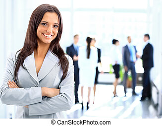 Successful business woman standing with her staff in...