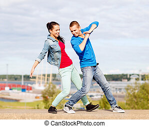 couple of teenagers dancing outside - summer holidays,...
