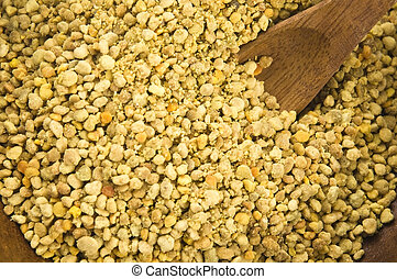 Bee pollen in wooden scoop Nutritional supplement