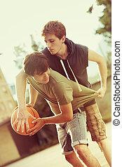 Street basketball - Boys playing a game of basketball on an...