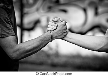 Let's stay friends - White teen and Black teen clasp hands...