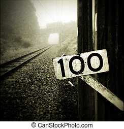 Railway - Sign next to railway tracks vanishing into the fog...