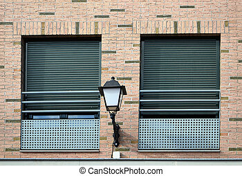 two windows and lamppost - two windows with green blinds and...