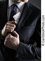 Businessman with ace card hidden under the jacket