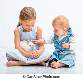 Little sisters with a rabbit