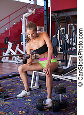 Active young woman works out with dumbell