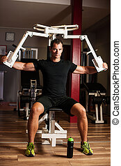Active sportsman works out in fitness on butterfly machine -...