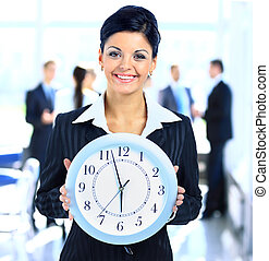 Young attractive business woman holding clock
