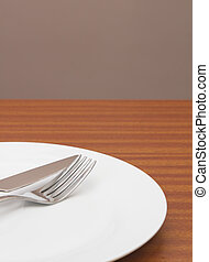 White place setting on  table with wall behind