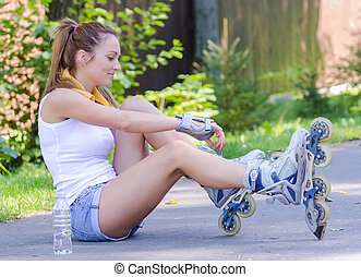 Young female skater sitting on the road and ties her rollers