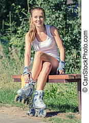 Smiling young woman on roller skates