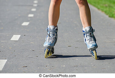 Close-up view of female legs in roller blades