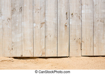wooden door on a sandy beach - wooden door and a rocky and...