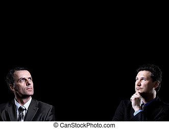 Two businessmen looking at the black background