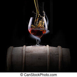 Cognac glass shrouded in a smoke on a black background
