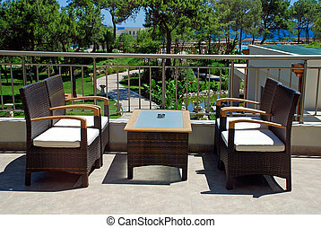 Rattan armchairs on terrace lounge in a luxury resort