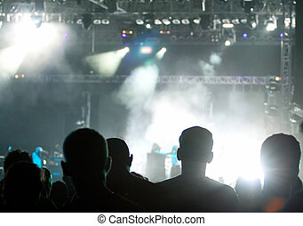 silhouettes of concert crowd in front of bright stage lights...