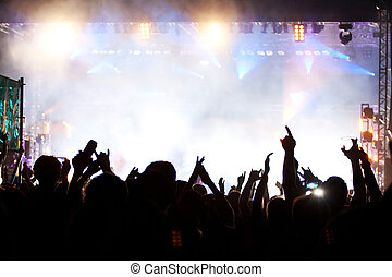 Crowd at concert in bright stage lights