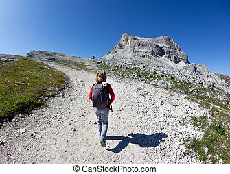 Young hiker walking on a mountain trail.