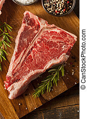Thick Raw T-Bone Steak with Seasoning and Rosemary