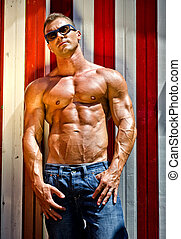 Handsome and muscular muscle man against beach changing room...