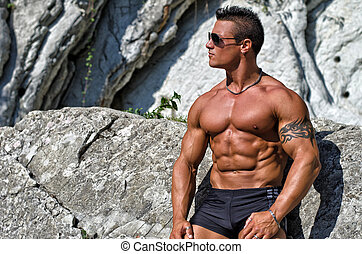 Handsome, muscular bodybuilder against white rocks -...