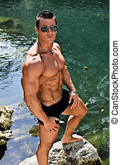 Attractive young bodybuilder standing in water pond -...