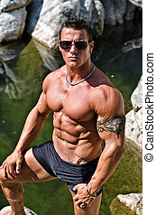 Handsome young muscle man standing in water pond -...