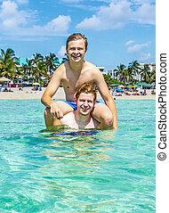 teen have fun playing piggyback in the ocean - handsome teen...