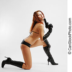 Girl with gun in kneeling position - Sexy woman stands on...