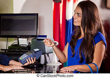 Paying at a cash register - Cute young woman paying with a...
