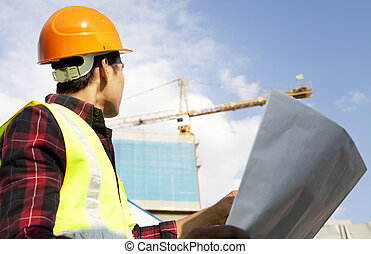Builder with blueprint at construction site
