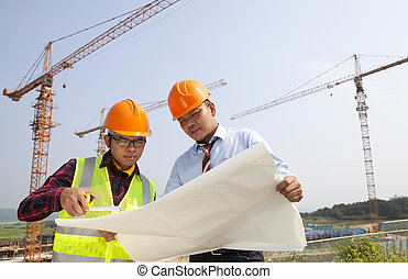 Young architects discussion in front of construction site -...
