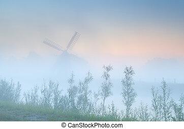 Dutch windmill in dense sunrise fog