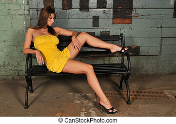 Brunette - Beautiful brunette in a yellow dress sitting on a...